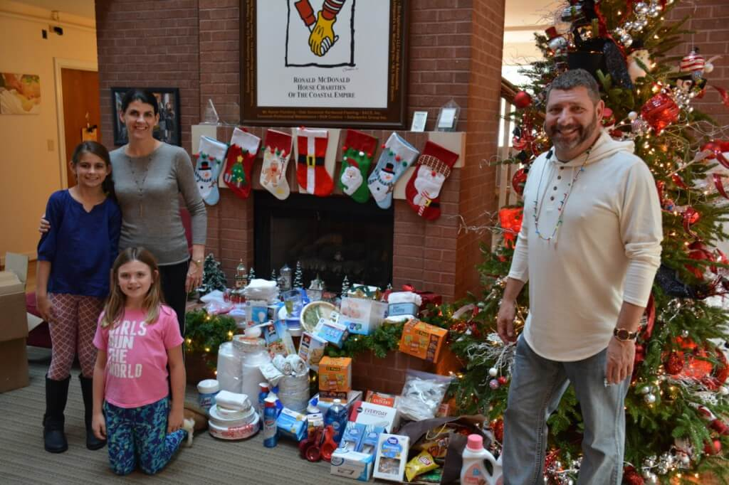 Mason Howington, Dr. Corinne Howington and Meg Howington (kneeling) drop off donated items to Bill Sorochak at the Ronald McDonald House of the Coastal Empire