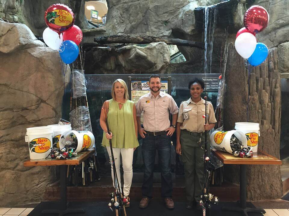 Chris Finnegan, Bass Pro Shop's Operations Manager (center), at the Bass Pro Shop Savannah Mall store presents donations to Hillari Keese Operations Manager for the Coastal Conservation Association's Savannah Chapter (left) and Nikki Bing, District Executive for the Coastal Georgia Council Boy Scouts of America (right).
