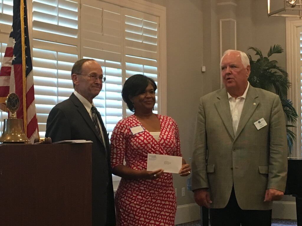 Left to Right Ben Gustafson President of Kiwanis presents grant to Junior Achievement of Georgia representatives Tom Stephens and Patrece B. Grant